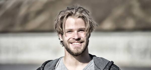 Guy with bearded face and blond hair haircut in grey tshirt happy smiling on sunny day outdoors, vintage filter. Fashion, beauty, skincare, hairdressing, barber salon concept.