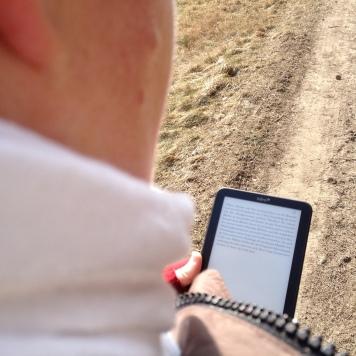 """Kerstin Cornils auf einem Spaziergang durch den Wald. Sie hält einen Tolino Shine in der Hand und liest """"Das Original"""" von John Grisham"""