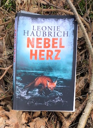 """Das Buch """"Nebelherz"""" von Leonie Haubrich posiert für ein Foto auf dem Waldboden"""