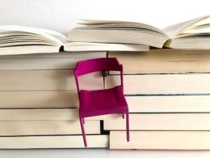 Peschka Pinker Stuhl am Bücherstapel