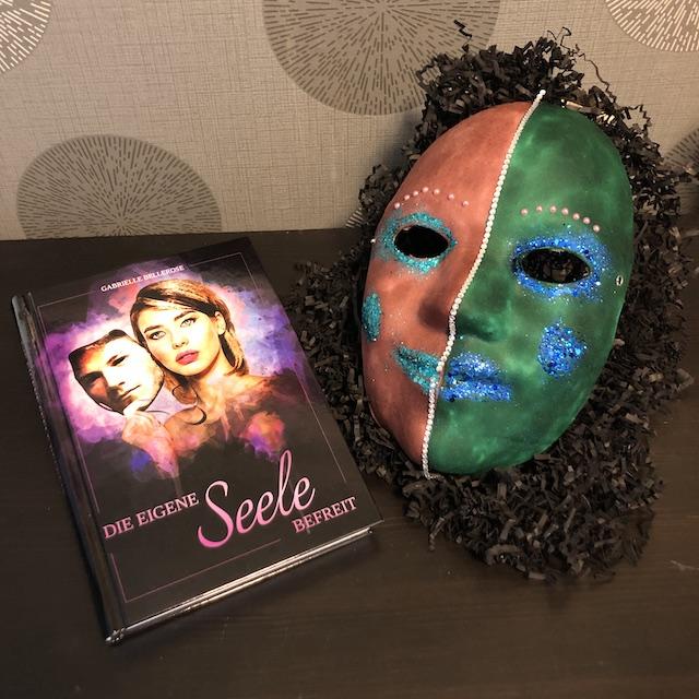 Die eigene Seele befreit von Gabrielle Bellerose Maske mit Buch liegend