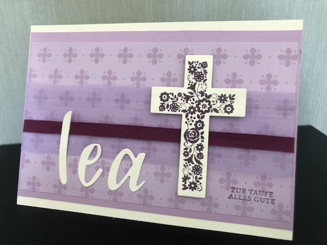 Zusehen ist eine selbst gebastelte Karte zur Taufe. Die Karte ist in lila Tönen gehalten, der Name Lea ist ausgestanzt auf die Karte geklebt, neben dem Namen ist ein florales Kreuz angebracht.