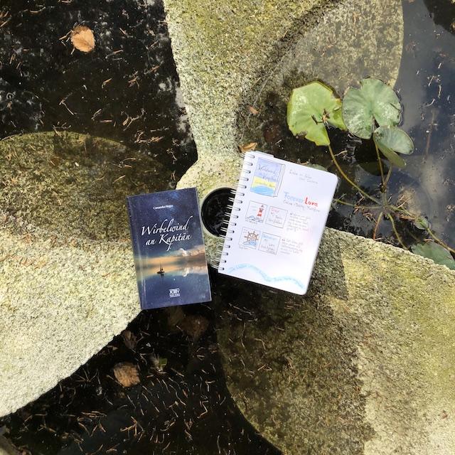 Foto vom Buch: Wirbelwind an Kapitän von Cassandra Negra. Das Buch liegt auf einer Schiffsschraube, auf dem Cover sieht man ein Segelboot Richtung Horizont fahren. Die Wolken spiegeln sich im Wasser. Neben dem Buch liegt ein Notizbuch mit Sketchnotes zum Roman