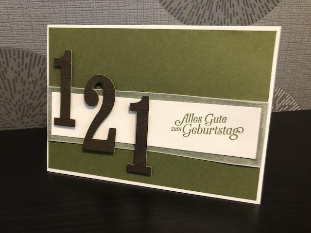 Zu sehen ist eine gebastelte Karte zum 121 Geburtstag. Die Karte ist grün, im unteren drittel ist ein weißer Streifen geklebt, dahinter schaut ein Organzaband heraus. Auf dem Streifen ist folgender Spruch gestempelt: Alles Gute zum Geburtstag. Daneben sind die Ziffern 1 2 2 in dunkelbraun erhaben aufgeklebt.