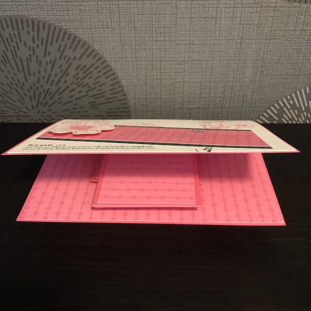 Zu sehen ist eine Pop Up Karte mit Flügeln. Auf der rosanen Grundkarte ist ein Auflieger in Vanille Pur geklebt. Dadrauf sind verschiedene Blüten in rosa gestempelt. Quer darüber liegen zwei Papierstreifen in dunkelgrün und rosa auf denen eine erhabene Blüte geklebt ist. Unter den Streifen ist ein Spruch gestempelt, der lautet: fei-ern (v) ein Fest zu Ehren von etwas oder jemandem begehen; einen frohen Anlass bejubeln; fröhlich beisammen sein.