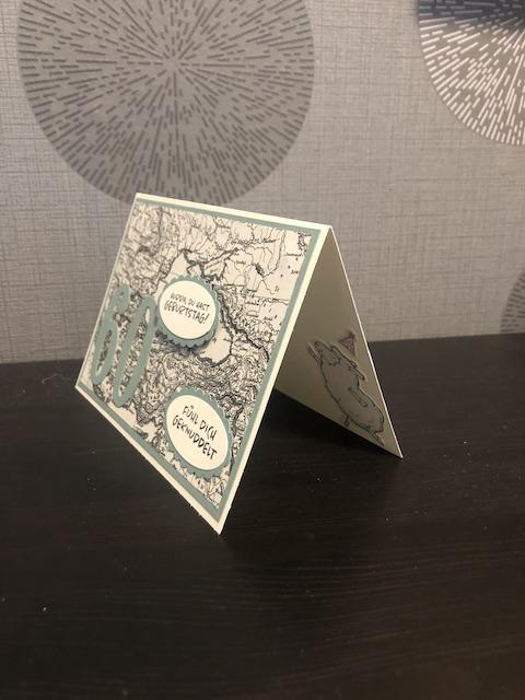 Zu sehen ist eine Geburtstagskarte mit einer 60 drauf. Der Hintergrund ist eine Landkarte in schwarz weiß. Zwei Texte sind auf der Karte angebracht: Hurra du hast Geburtstag, Fühl dich geknuddelt. Im Innenteil ist ein tanzendes Schaf mit Partyhut zu sehen.