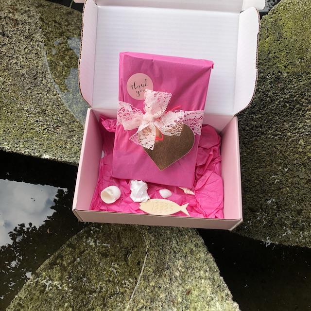 Auf dem Foto ist ein Buchpaket zu sehen. Das Buch ist in rosanes Seidenpapier eingeschlagen und mit einer Schleife aus Spitzenband verschlossen. Im Paket liegen Muscheln.