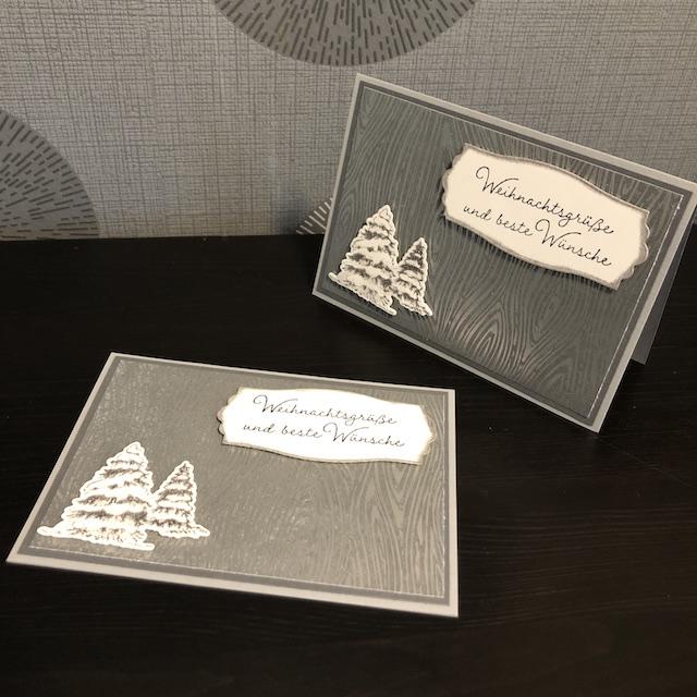 Weihnachtskarte mit silberner Holzmaserung, zwei Tannenbäumen und einem Etikett mit dem Spruch: Weihnachtsgrüße und beste Wünsche