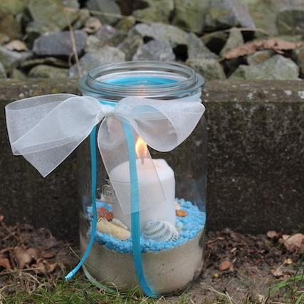 Ein 1,5l Einmachglas gefüllt mit Vogelsand. Darüber sind blaue Steinchen gestreut auf denen Muscheln und Schnecken aus dem Meer liegen. In der Mitte steckt eine weiße Stumpen Kerze. Das Weckglas ist oben mit einer weißen Taftschleife versehen und blauen Bändern.