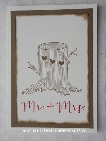 Grußkarte zur Hochzeit. Abgebildet ist ein Baumstumpf an dem einen Kette mit drei Herzen hängt. Darunter stehen die Worte Mr. + Mrs. in rot gestempelt.